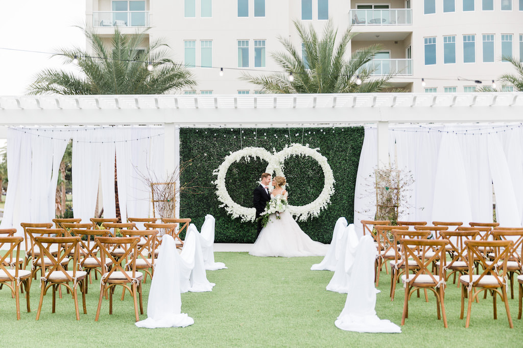 Modern, Elegant Florida Bride and Groom, At Garden Inspired Outdoor Wedding Ceremony, Gazebo Alter, Luxurious Infinity Ring Hanging Floral Arrangement with White Orchids, Dark Green Boxwood Wall, Wood Cross Back Chairs, Draping   Tampa Bay Wedding Planner Special Moments Event Planning   Tampa Bay Wedding Florist Gabro Event Services