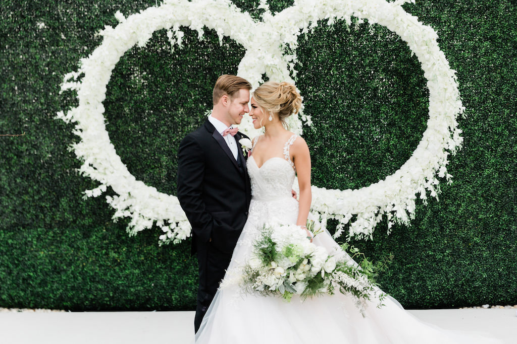 Modern, Elegant Florida Bride and Groom, Wearing White Ballgown Style Wedding Dress with Sweetheart Neckline and Illusion Lace Straps, Carrying Luxurious White and Green Bouquet with Mixed Stems, At Garden Inspired Outdoor Wedding Ceremony, Infinity Ring Hanging Floral Arrangement with White Orchids, Dark Green Boxwood Wall, Wood Cross Back Chairs, Draping   Tampa Bay Wedding Planner Special Moments Event Planning   Tampa Bay Wedding Florist Gabro Event Services   Tampa Bay Hair and Makeup Artists Femme Akoi   Tampa Bay Couture Wedding Dress Boutique Isabel O'Neil Bridal Collection