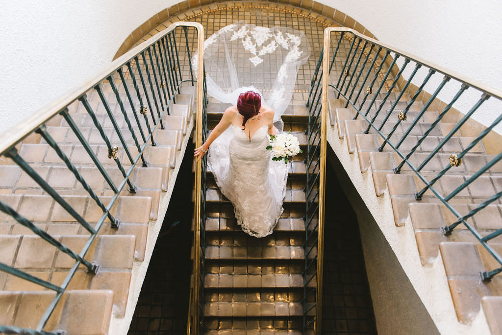 Creative Bridal Wedding Portrait   Bride on Staircase Wearing Cathedral Length Veil Holding Ivory, White Floral Bouquet   Wedding Photographer Kera Photography   Destiny and Light Hair and Makeup Group