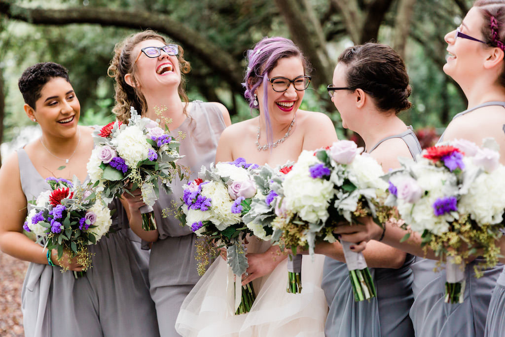 Modern, Colorful Florida Bride and Bridesmaids in Clearwater Park, Purple and Grey Ombre Mix and Match Long Bridesmaid Dresses, Holding Whimsical Floral Bouquet Purple, Ivory, White, Red, Flowers with Greenery