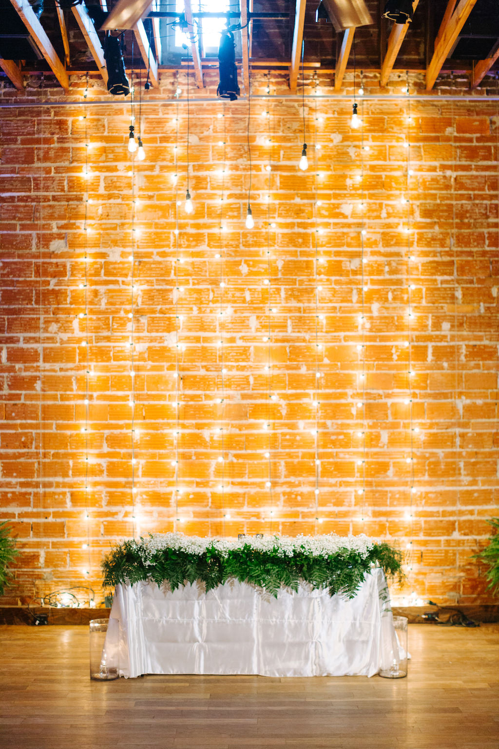 Modern, Romantic Reception and Florida Wedding Decor, Sweetheart Table, with Babies Breath Garland Florals, String light Backdrop on Exposed Brick Wall | Tampa Bay Premier Wedding Venue NOVA 535 in Downtown St. Pete