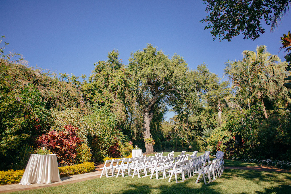 Simple Garden Wedding Ceremony Decor, Folding White Chairs, Two Tall Round Tables with White Linens | Outdoor Tropical Inspired St. Pete Wedding Venue | Sunken Gardens