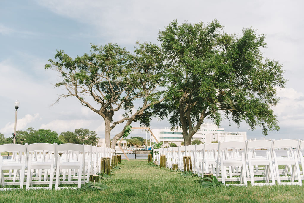 Modern Simple Outdoor Waterfront Wedding Ceremony Decor, White Folding Chairs, Wooden Pedestals Lining Aisle, Unique Wooden Geometric Wedding Arch | Wedding Photographer Kera Photography | St. Petersburg Wedding Venue The Poynter Institute
