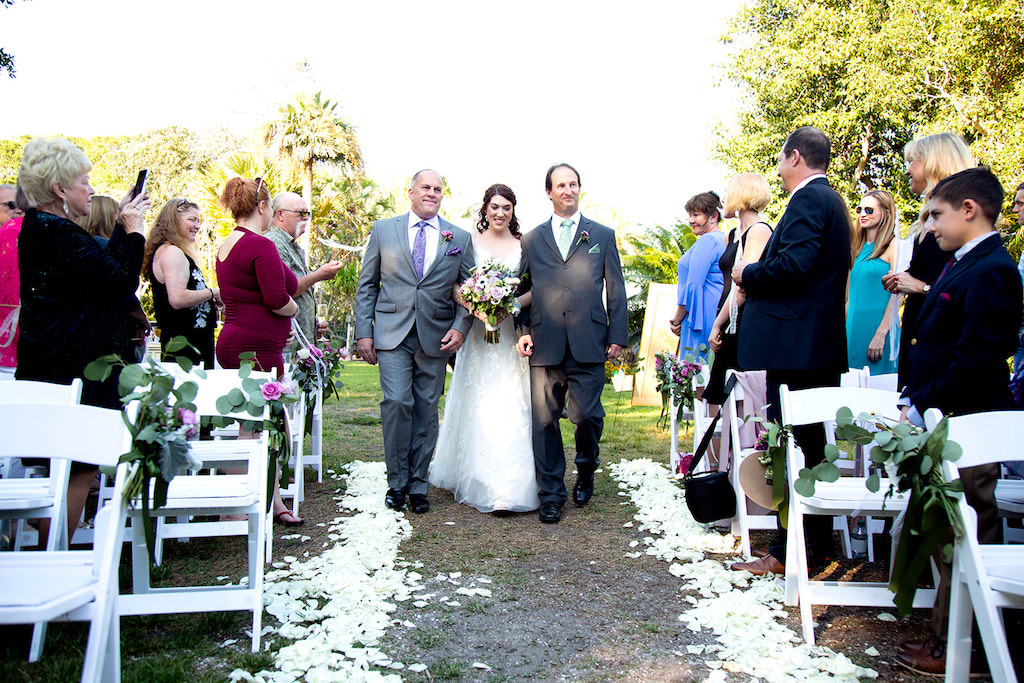 Elegant, Classic Wedding Ceremony Bride and Father Walk Down the Aisle Processional Portrait, White Flower Petals, Greenery Eucalyptus, Purple Flowers on White Folding Chairs | Sarasota Wedding Planner Laura Detwiler Events