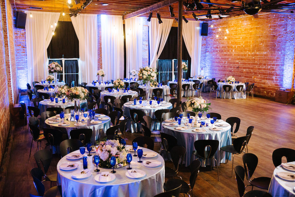 Modern, Romantic Reception and Florida Wedding Decor, Tall Floral Centerpieces with White, Peach, Pink, Ivory Flowers, Round Tables with Silver Tablecloths, Blue Stemware, Exposed Brick Wall | Tampa Bay Premier Wedding Venue NOVA 535 in Downtown St. Pete