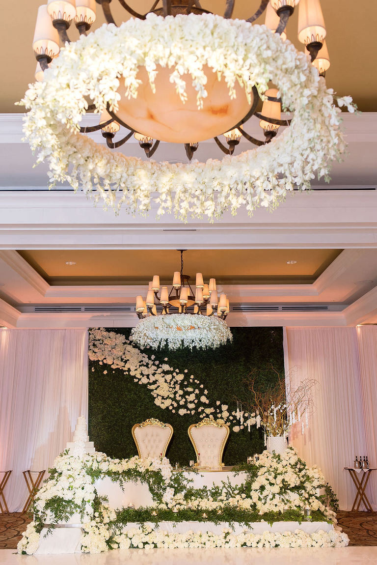 INSTAGRAM SWIPE Elegant Stunning Classic Wedding Reception Decor, White Flowers Hanging From Chandelier, Sweetheart Table with Victorian Style Gold and Ivory Bride and Groom Chairs, Greenery and Lush White, Ivory Florals on Sweetheart Table, Greenery and White and Ivory Cascading Floral Backdrop and White Draping | Tampa Bay Wedding Photographer Kristen Marie Photography | Clearwater Beach Wedding Venue Sandpearl Resort | Wedding Florist, Rentals Linens, Lighting and Draping Gabro Event Services | Wedding Day of Coordinator Special Moments Event Planning