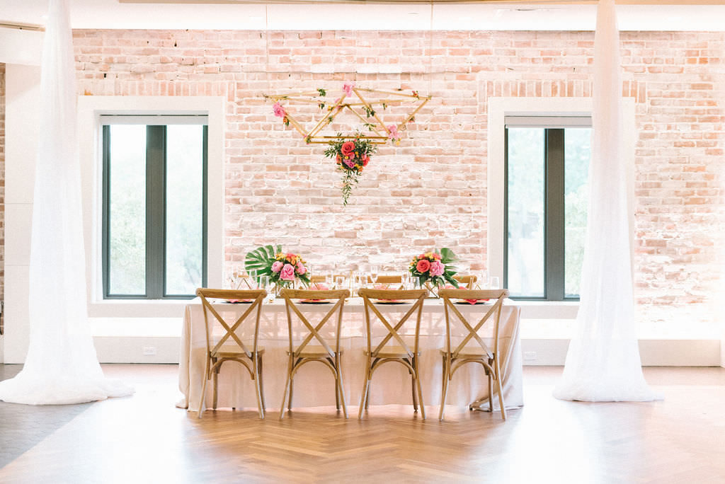 Modern Colorful Tropical Wedding Reception Decor, Feasting Table with Sheer White Linen, Wooden Crossback Chairs, Pink and Yellow Flowers and Green Monstera Palm Leaf Centerpieces, Hanging Gold Geometric Chandelier with Orange, Pink and Greenery Floral Arrangement | Tampa Bay Wedding Photographer Kera Photography | Downtown St. Pete Modern Wedding Venue Red Mesa Events | Wedding Florist and Rentals Gabro Event Services | Wedding Linen and Tabletop Rentals Kate Ryan Event Rentals | Wedding Planner UNIQUE Weddings & Events