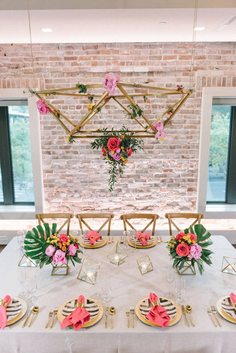 Modern Colorful Tropical Wedding Reception Decor, Feasting Table with Sheer White Linen, Wooden Crossback Chairs, Pink and Yellow Flowers and Green Monstera Palm Leaf Centerpieces, Hanging Gold Geometric Chandelier with Orange, Pink and Greenery Floral Arrangement, Gold Chargers and Plates with Bright Pink Linen with Gold Napkin Ring | Tampa Bay Wedding Photographer Kera Photography | Downtown St. Pete Modern Wedding Venue Red Mesa Events | Wedding Florist and Rentals Gabro Event Services | Wedding Linen and Tabletop Rentals Kate Ryan Event Rentals | Wedding Planner UNIQUE Weddings & Events