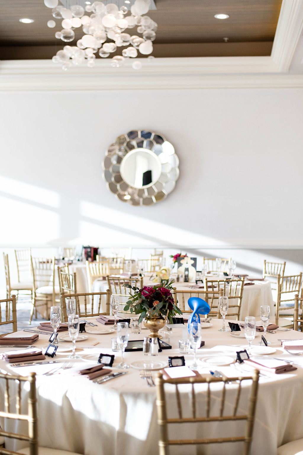 Classic Elegant Wedding Reception Decor, Round Tables with Champagne Linen, Gold Chiavari Chairs, Low Gold Vase with Red and Greenery Floral Centerpiece | Clearwater Beach Wedding Venue Hyatt Regency Clearwater Beach| Wedding Rentals Over the Top Rental Linens