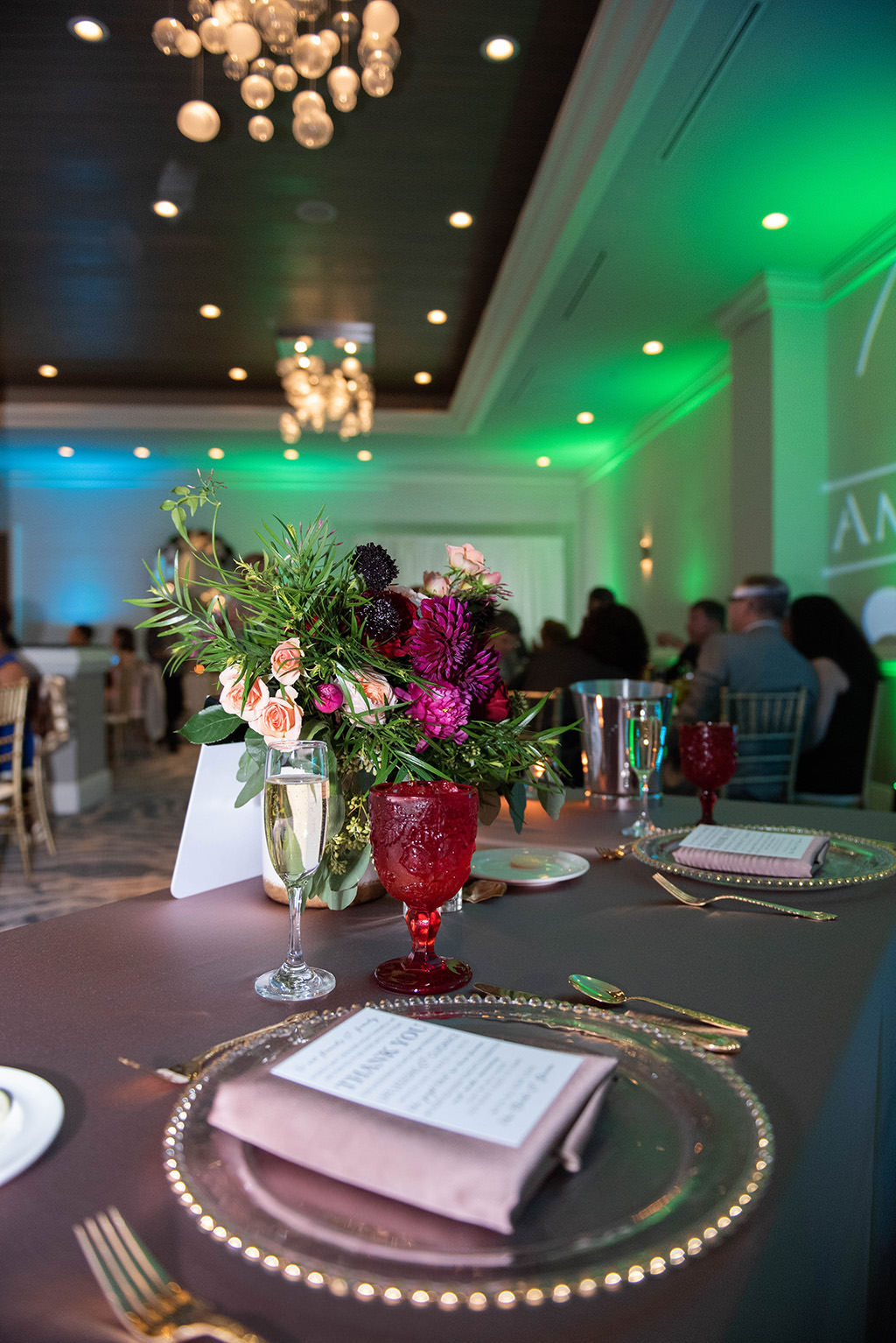 Tampa Classic Elegant Wedding Reception Decor, Clear Glass and Gold Bead Rimmed Charger Plates, Blush Pink Linen, Blush Pink, Purple, and Greenery Floral Centerpiece, Green Uplighting | Custom Tampa Wedding Uplighting by Gabro Event Services