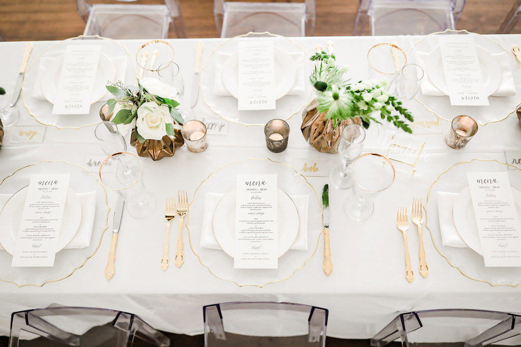 Classic Neutral Wedding Reception Decor, Long Feasting Table with White Linen, Clear Glass and Gold Rimmed Charger, Gold Silverware, Low Gold Vase with Greenery and Ivory Floral Centerpieces, Gold Mercury Candles | Tampa Bay Wedding Photographer Lifelong Photography Studio | Wedding Rentals Kate Ryan Event Rentals