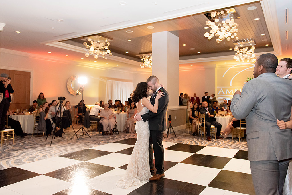 Romantic Bride and Groom First Dance Wedding Reception Portrait on Black and White Checkered Dance Floor, Modern Chandeliers | Clearwater Beach Wedding Venue Hyatt Regency Clearwater Beach | Clearwater Beach Wedding and Event Rentals by Gabro event Services