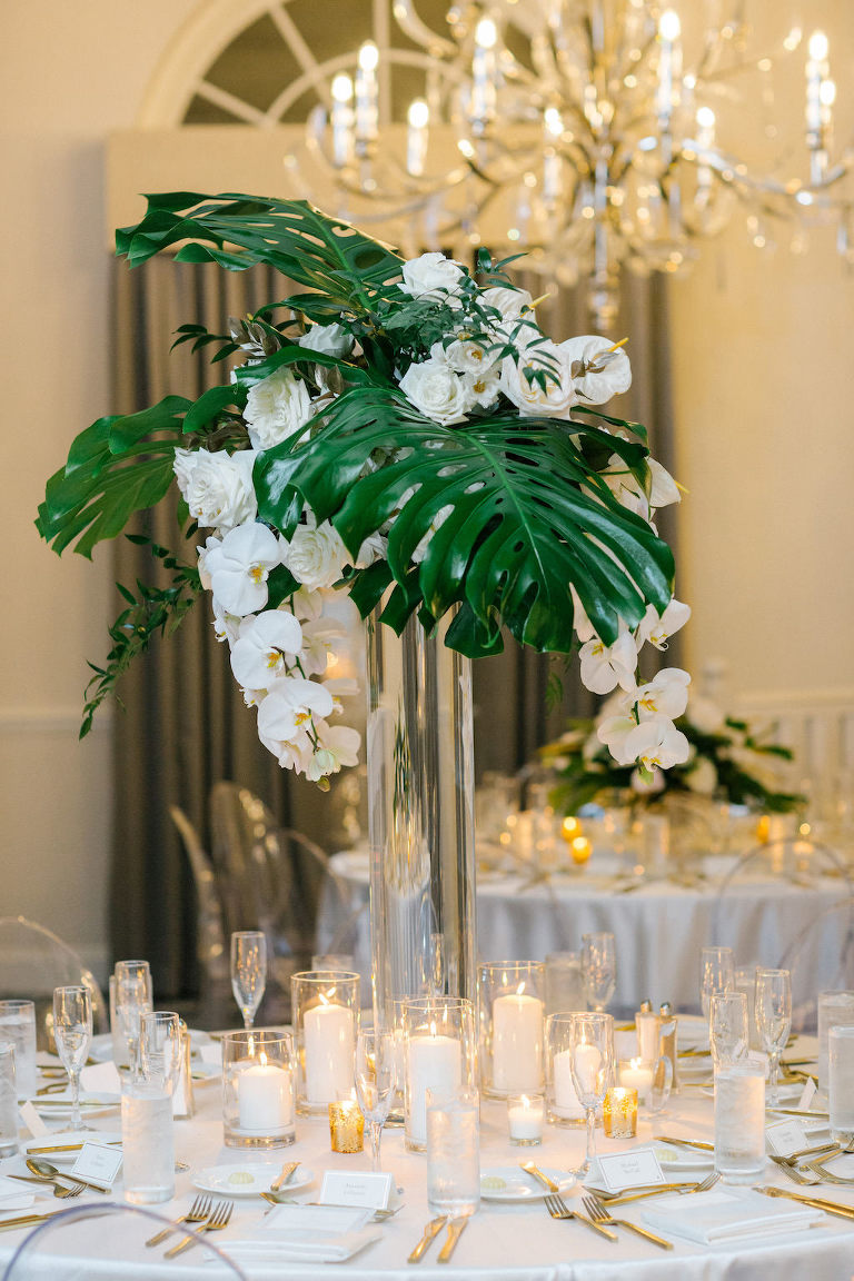 Tropical Modern Elegant Wedding Reception Decor, Tall Glass Cylinder Vase with Monstera Palm Leaf and White Orchids Floral Centerpiece | Tampa Bay Wedding Planner Parties A'La Carte | Wedding Florist Bruce Wayne Florals | Wedding Flatware Rentals from A Chair Affair