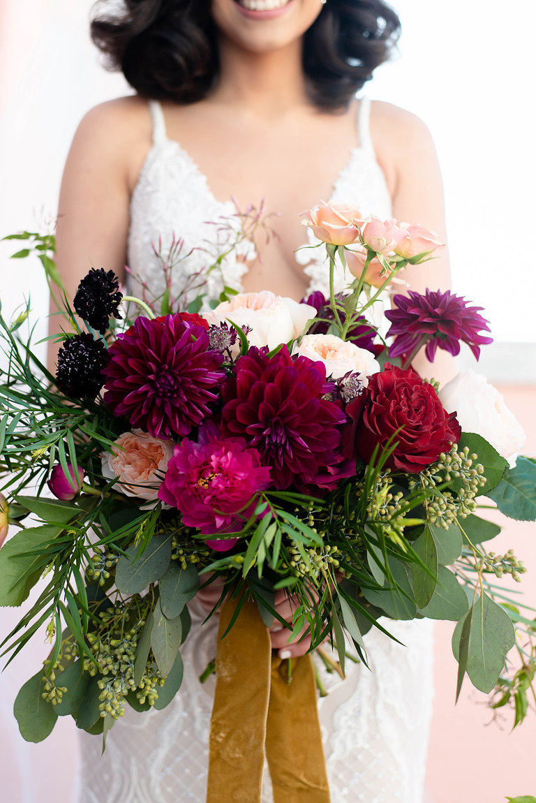 Tampa Bay Bride Holding Jewel Toned Organic Bridal Bouquet, Red, Dark Purple, Pink, Maroon, Blush Pink Floral Bouquet with Greenery and Satin Ribbons
