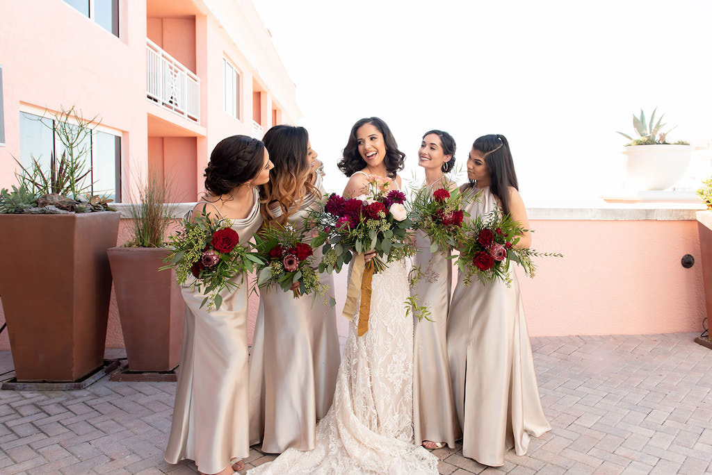 Clearwater Beach Bride Holding Organic Red, Maroon, Greenery and Blush Pink Floral Bouquet with Bridesmaids in Champagne Mix and Match Floor Length Dresses Hotel Rooftop Wedding Portrait | Tampa Bay Wedding Dress Shop Isabel O'Neil Bridal | Wedding Attire Bella Bridesmaids | Waterfront Clearwater Beach Wedding Venue Hyatt Clearwater Beach