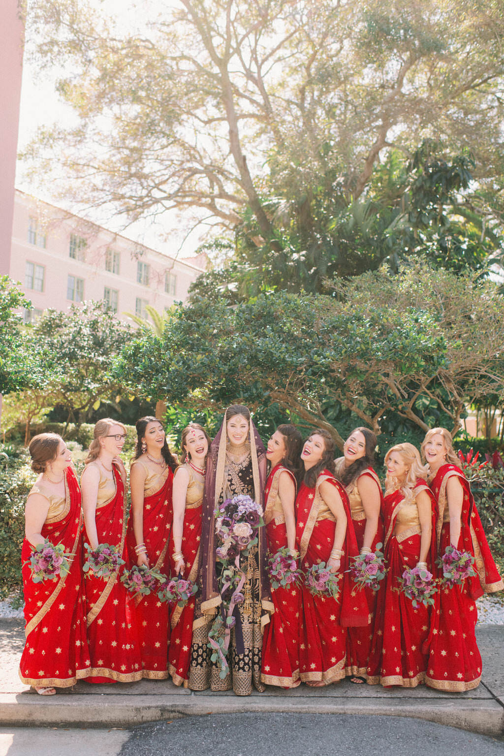 St. Pete Traditional Indian Hindu Bride and Bridal Party Portrait, Bridesmaids in Luxurious Red and Gold Saris Holding Purple and Green Floral Bouquets | Tampa Bay Bridal Hair and Makeup Artist Michele Renee The Studio