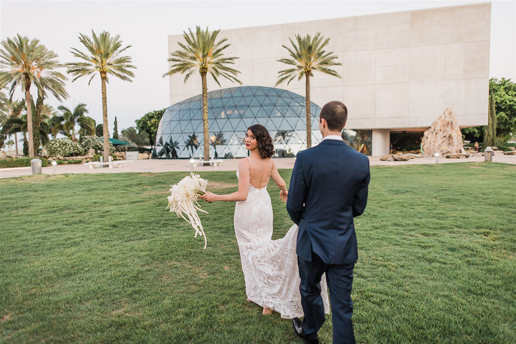 Tampa Bride and Groom Wedding Portrait, Groom Holding Train of Bride's Hayley Paige Lace Open Back Wedding Dress with St. Petersburg Salvador Dali Museum Glass Dome Wedding Venue Backdrop