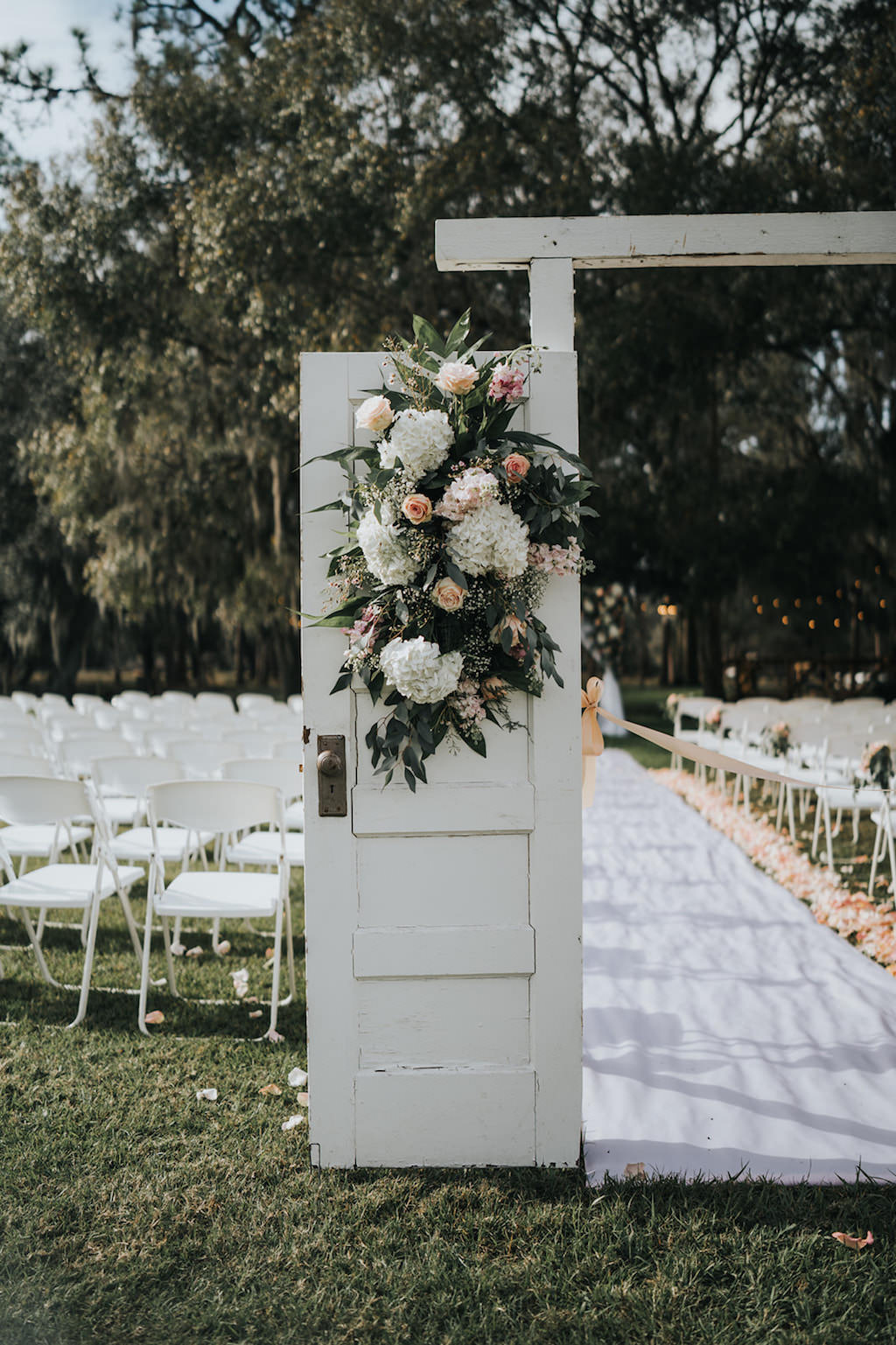 Rustic Chic Outdoor Wedding Ceremony Decor, Wooden Door Entry with White Hydrangeas, Blush Pink Roses and Greenery Floral Arrangement   Tampa Wedding Venue Rafter J Ranch   Wedding Planner Kelly Kennedy Weddings and Events