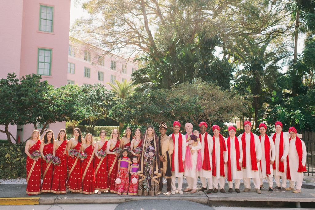 St. Petersburg Traditional Indian Hindu Bride and Groom, Wedding Party Portrait, Bridesmaids in Luxurious Red and Gold Saris Holding Purple and Green Floral Bouquets, Groomsmen in White and Red Sherwani and Turbans, Flower Girls in Purple, Red and Gold Saris