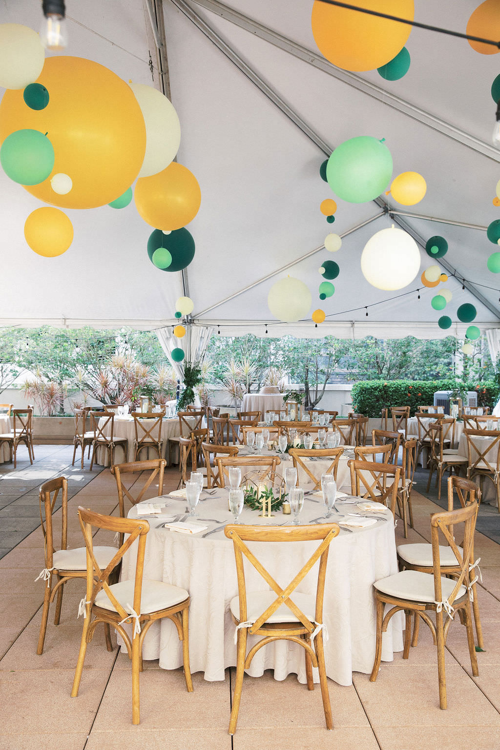 Whimsical Rustic Elegant Tent Wedding Reception Decor, Round Tables with Ivory Linens, Wooden Crossback Chairs, Green, Yellow and White Hanging Balloons | Tampa Bay Wedding Venue The Epicurean Hotel