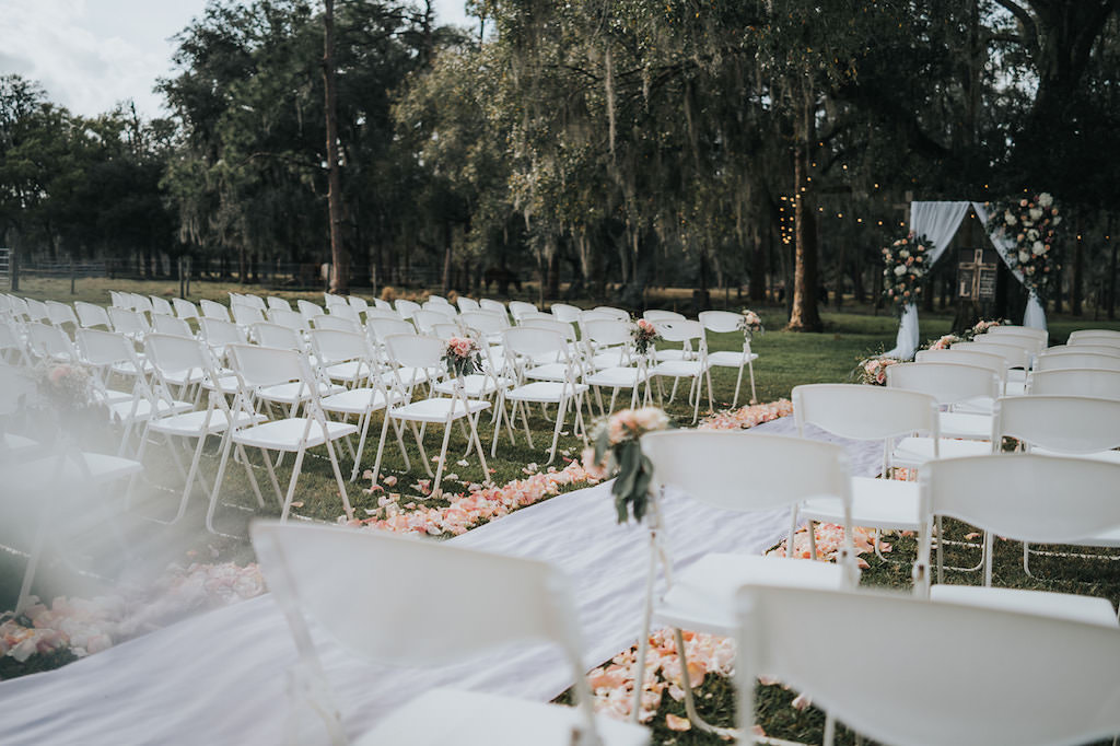 Rustic Chic Wedding Ceremony Outdoor Decor, White Folding Chairs with Blush Pink and White Floral Arrangements, Flower Petal and White Linen Aisle Runner, Linen Draping Arch with Floral Arrangements   Tampa Wedding Venue Rafter J Ranch   Wedding Planner Kelly Kennedy Weddings and Events