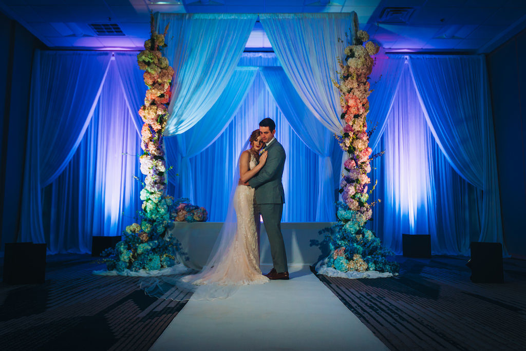 Florida Bride and Groom Intimate Wedding Portrait, Unique Modern Contemporary Wedding Ceremony Decor, Blue Uplighting, Hanging Drapery Backdrop, Tall Large Colorful Floral Pillars by Gabro Event Services | Tampa Bay Boutique Hotel Wedding Venue Hotel Alba | Wedding Planner Special Moments Event Planning | Styled Shoot