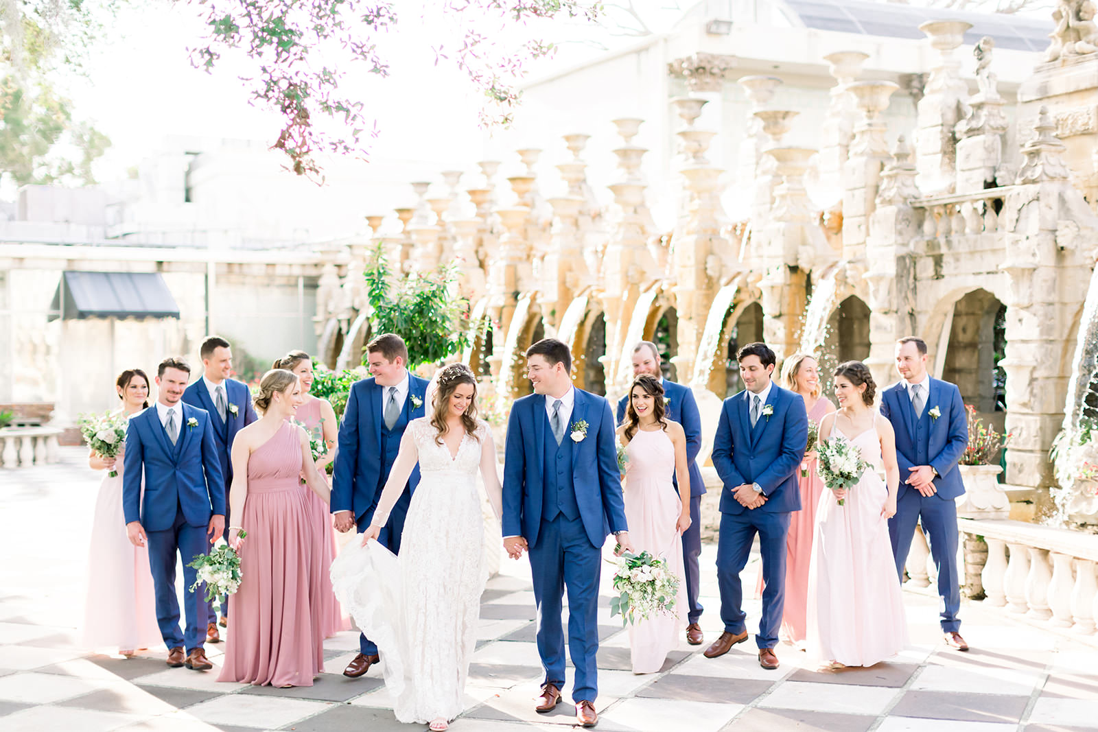 Florida Bride and Groom with Wedding Party in Outdoor Garden Courtyard, Bridesmaids in Mix and Match Pink Dresses, Groomsmen in Navy Suits | Tampa Bay Wedding Photographers Shauna and Jordon Photography