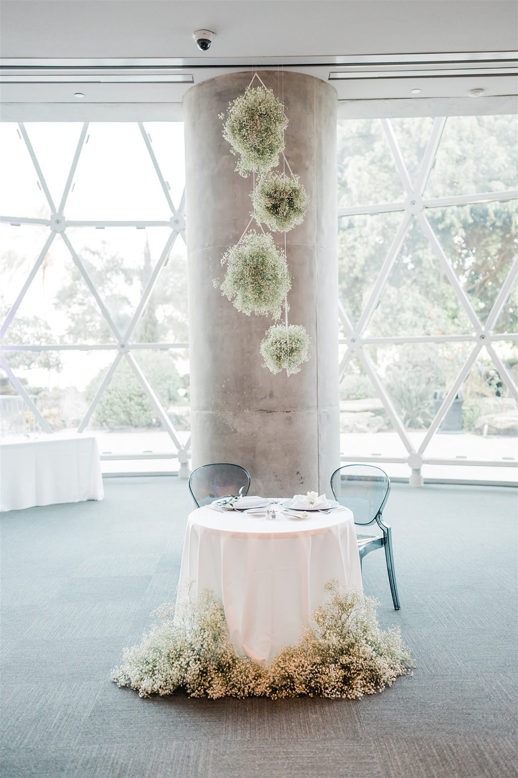 Elegant Whimsy Wedding Reception Decor, Round Sweetheart Table with Blush Pink Linen, White Baby's Breath Floral Arrangements, Hanging White Round Flowers | Tampa Wedding Planner and Florist John Campbell Weddings