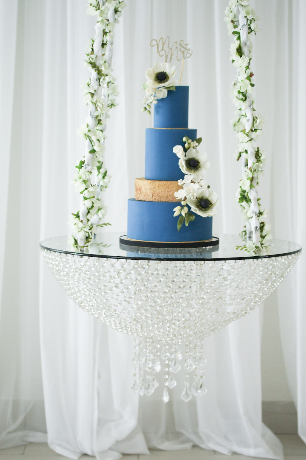 Tampa Wedding Cakes and Desserts | Tampa Bay Cake Company | Dusty Blue and Gold Round Wedding Cake on Hanging Cake Stand with White Floral Accent