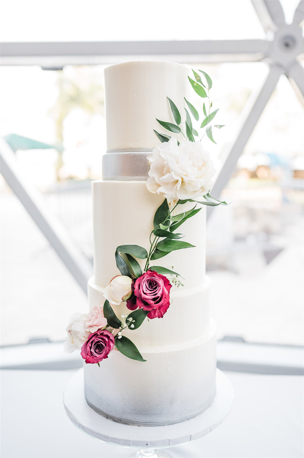 Modern White with Silver Accent Four Tier Wedding Cake with Cascading Magenta Pink and White with Greenery Flowers | St. Pete Wedding Cake Bakery The Artistic Whisk | Tampa Wedding Planner and Florist John Campbell Weddings