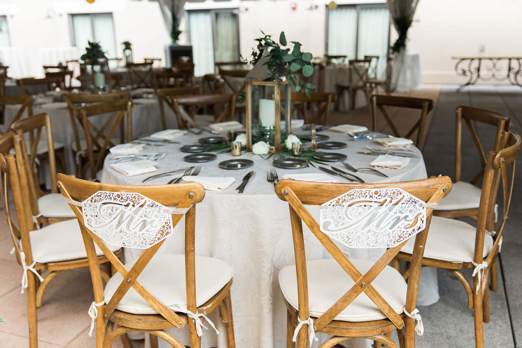 Tampa Rustic Elegant Wedding Reception Decor, Round Tables with Ivory Linen, Wooden Crossback Chairs with Lace Mr and Mrs Chair Signs, Wooden and Silver Lantern Centerpiece with Silver Dollar Eucalyptus