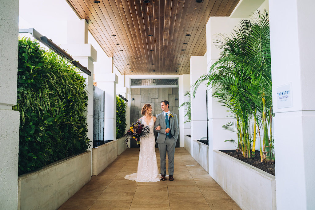 Florida Bride and Groom Wedding Portrait in Boutique Tampa Hotel Alba Hallway, Bride in Lace and Illusion Deep V Neckline Fitted Silhouette Wedding Dress, Groom in Grey Suit with Blue Tie | Wedding Attire Truly Forever Bridal | Styled Shoot