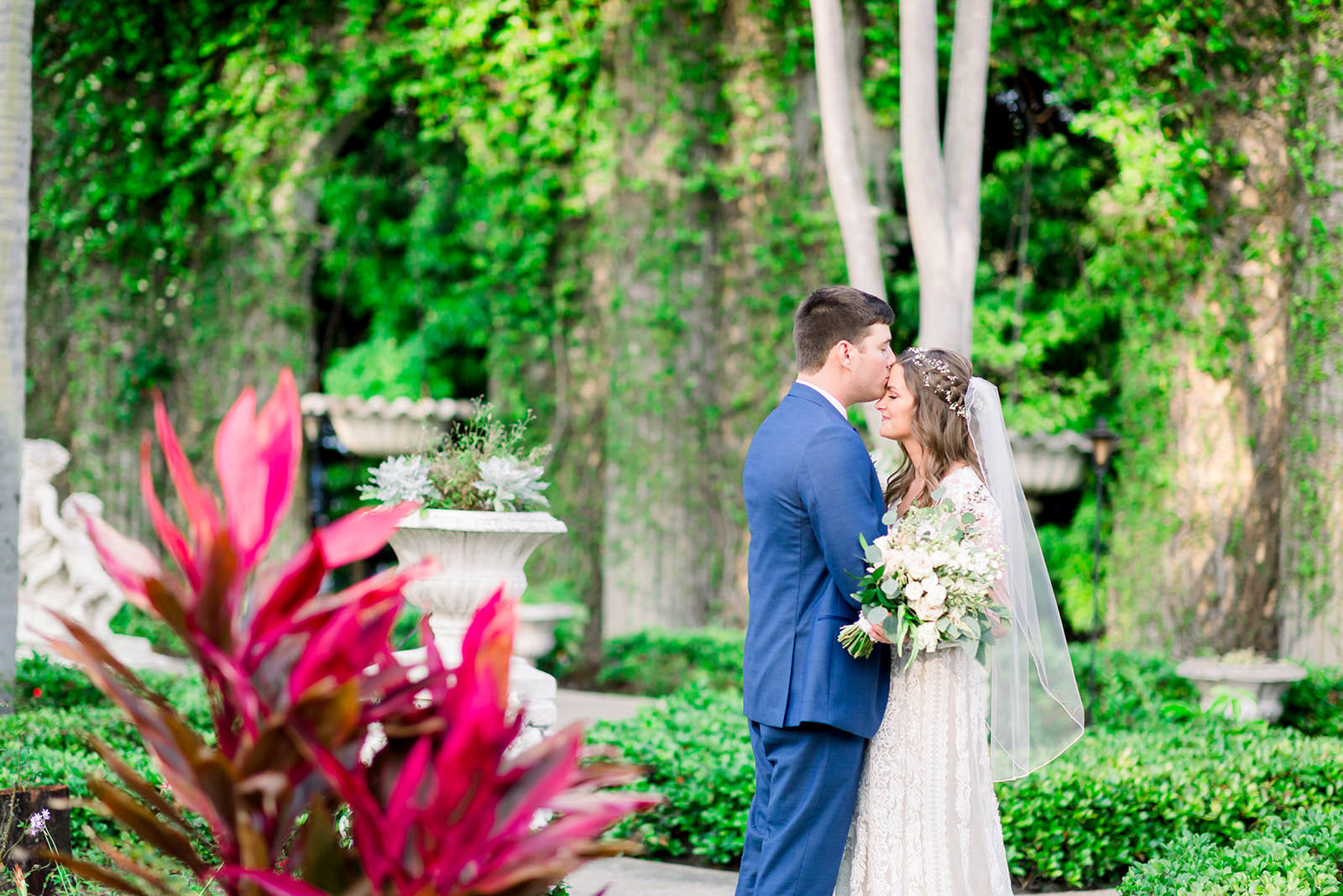 Boho Inspired Florida Bride and Groom in Outdoor Garden Courtyard, Groom in Navy Suit, Bride Holding White Floral Bouquet with Greenery Wedding Portrait | Tampa Bay Wedding Photographers Shauna and Jordon Photography