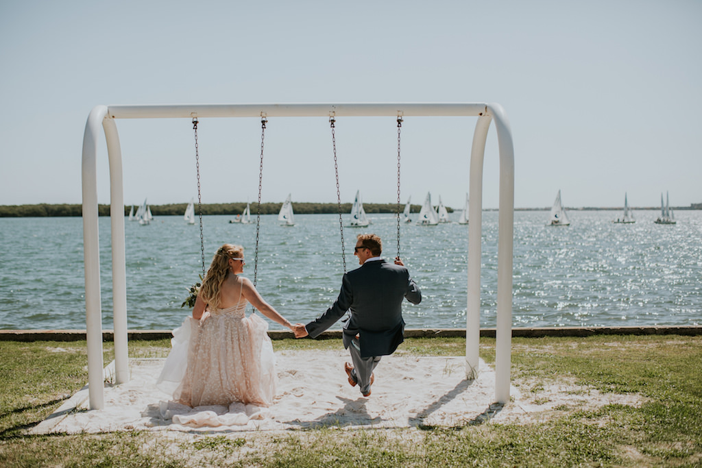 Fun Creative Tampa Bay Bride and Groom Holding Hands on Swing , St. Pete Waterfront Wedding Portrait | UNIQUE Weddings + Events