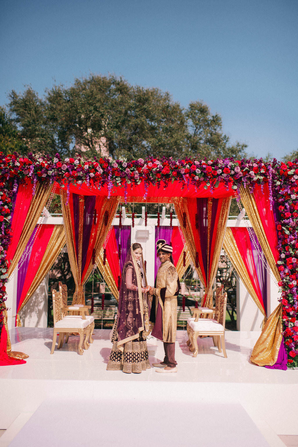 Luxurious Indian Hindu Traditional Wedding Ceremony Portrait of Bride and Groom Under Elegant Red, Gold and Purple Draping with Extravagant Colorful Lush Red, Purple, Plum, Lilac Floral Arrangements | St. Pete Wedding Venue North Straub Park