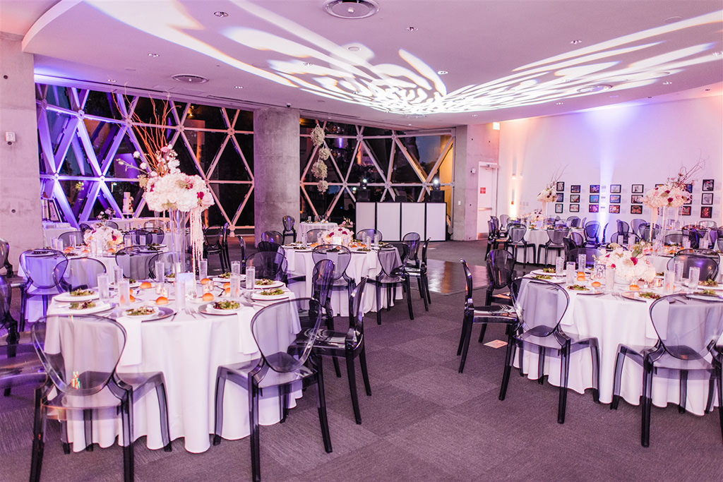 Downtown St. Pete Ivory and Blush Wedding Reception with Grey Ghost Chairs at Salvador Dali Museum | St. Pete Wedding Planner and Florist John Campbell Weddings | Catering by Olympia Catering | GOBO Light and Rentals by Gabro Event Services