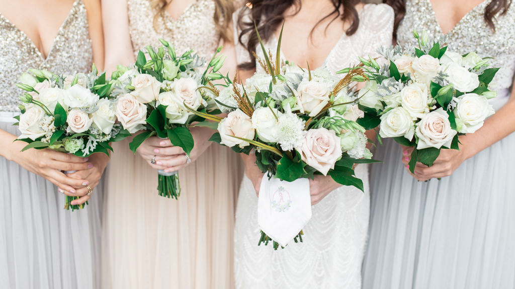 Florida Bride and Bridesmaids in Mix and Match Silver, Gray and Nude Dresses Holding Garden Inspired Blush Pink and Ivory Roses with Yellow and Green Leaves and Dusty Miller Floral Bouquets