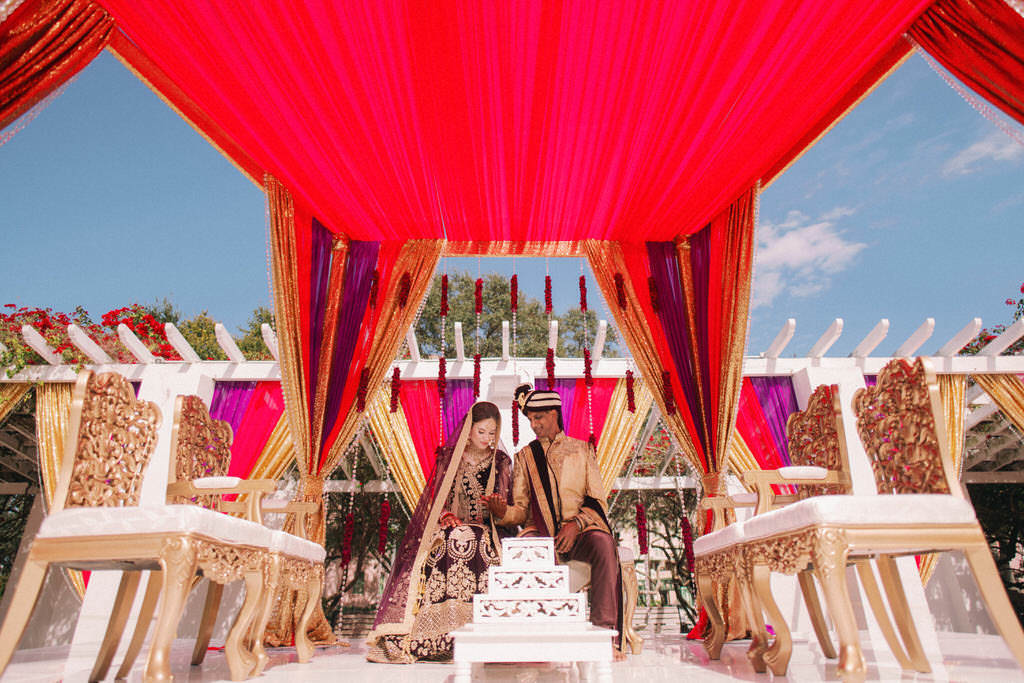Tampa Bay Luxurious Indian Hindu Traditional Wedding Ceremony Portrait of Bride and Groom Under Elegant Lush Red, Gold and Purple Draping, Elegant Gold and Ivory Cushion Chairs | St. Petersburg Wedding Venue North Straub Park