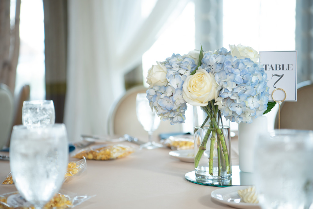 Classic Wedding Reception Decor, Low Floral Centerpiece and Table Number, with Dusty Blue Hydrangeas, Ivory Rose Floral Arrangement in Glass Vase   Tampa Bay Luxury Wedding Planner Coastal Coordinating