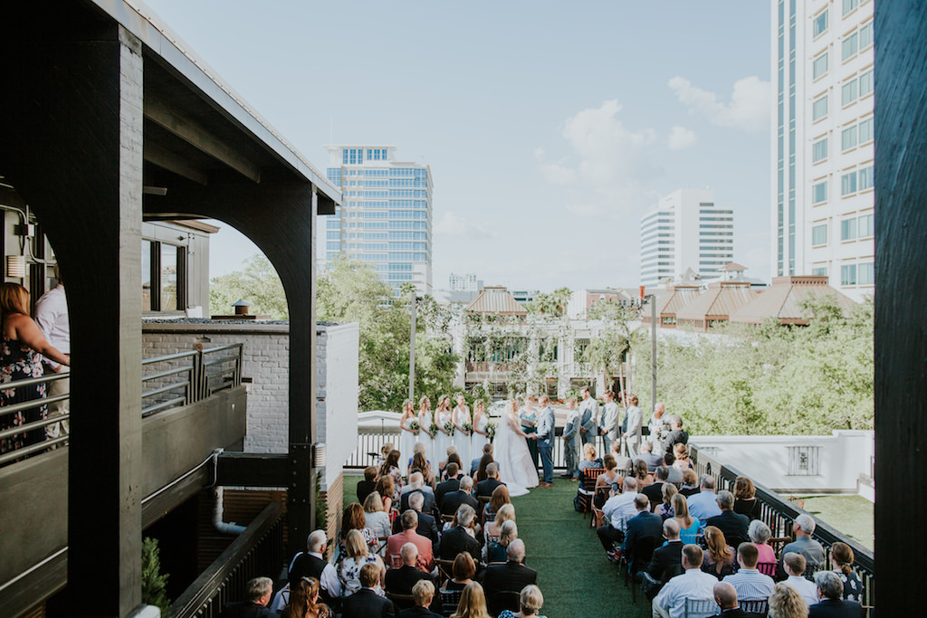 Outdoor Rooftop Wedding Ceremony Bride and Groom Exchanging Vows Wedding Portrait | Downtown St. Pete Wedding Ceremony Rooftop Venue Station House