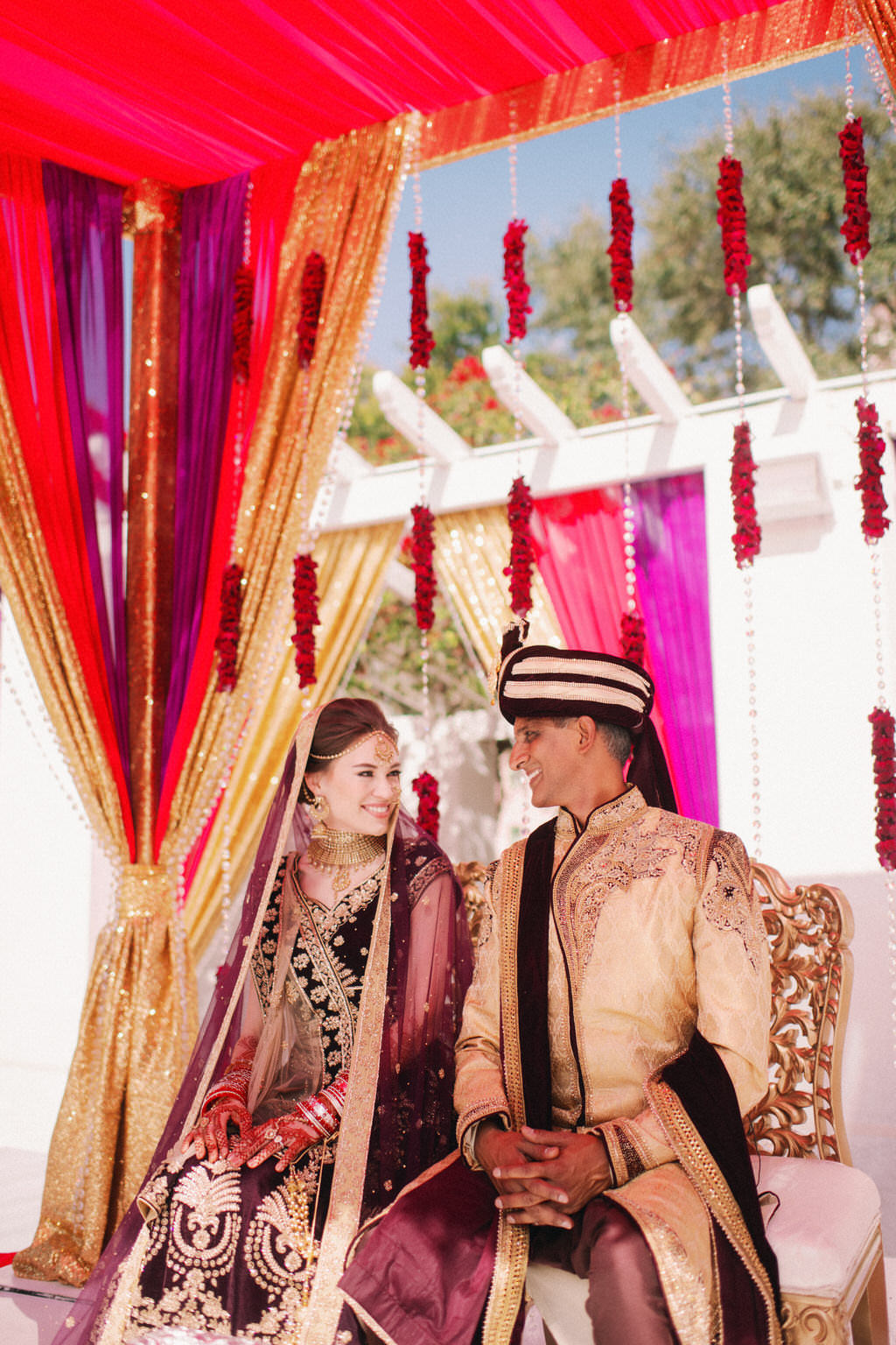 Tampa Luxurious Indian Hindu Traditional Wedding Ceremony Portrait of Bride and Groom Under Elegant Lush Red, Gold and Purple Draping, Hanging Red Floral and Crystals, Bride in Custom Purple Velvet, Gold and Black Lehenga, Groom in Black and Gold Sherwani and Turban