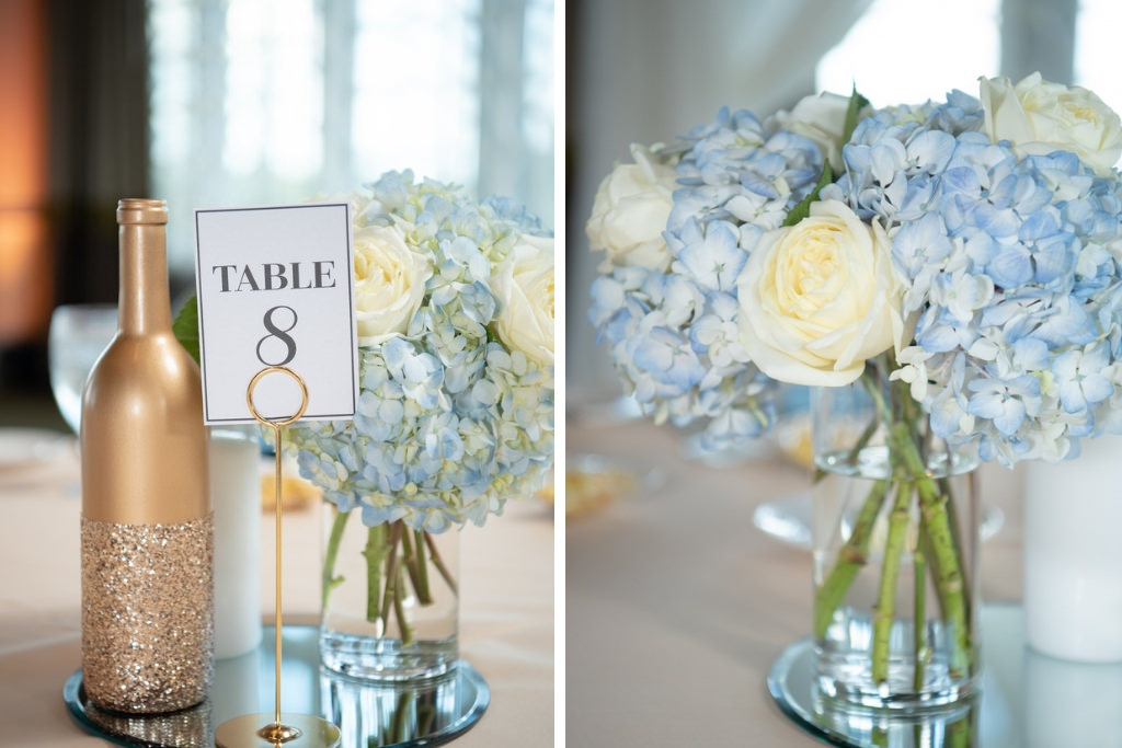 Classic Wedding Reception Decor, Low Floral Centerpiece, Decorative Gold Wine Bottle, and Table Number, with Dusty Blue Hydrangeas, Ivory Rose Floral Arrangement in Glass Vase   Tampa Bay Luxury Wedding Planner Coastal Coordinating