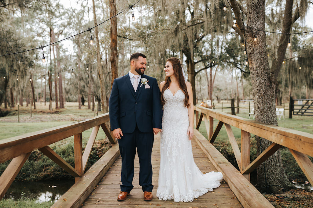 Rustic Chic Bride and Groom on Wooden Bridge Outdoor Wedding Portrait, Bride in Lace and Illusion V Neckline Wedding Dress, Groom in Blue Suit with Blush Pink Tie   Parrish Wedding Venue Rafter J Ranch