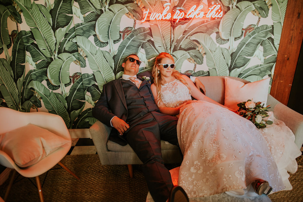 Fun Creative Bride and Groom with Sunglasses Lounging on Couch and Palm Tree Leaf Wallpaper Backdrop, Bride in Floral Lace and Illusion Halter Neckline Wedding Dress | Downtown St. Pete Wedding Venue Station House