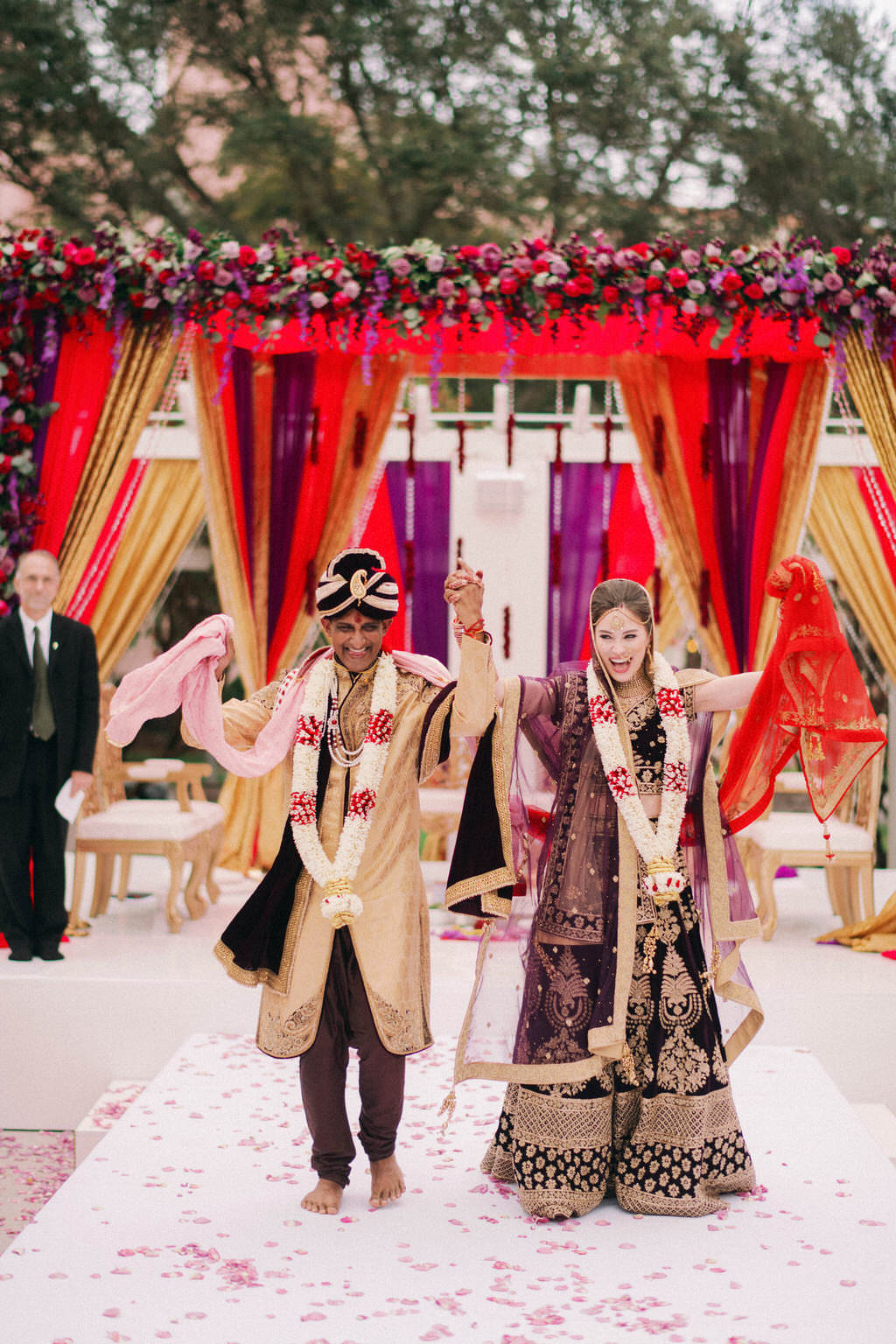 Tampa Bay Traditional Colorful Elegant Indian, Hindu Wedding Ceremony Bride and Groom Recessional Portrait, Bride in Custom Purple Velvet, Gold and Black Lehenga, Groom in Black and Gold Sherwani and Turban, Luxurious Red, Purple and Gold Linen Draping Altar, Lush Purple, Lilac, Plum, and Red Floral Arrangements, Hanging Red Floral and Crystals