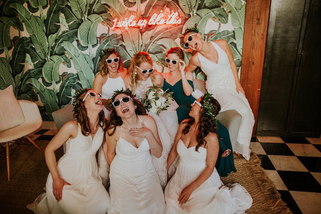 Fun Creative Bridal Party Portrait | Bridesmaids in Mix and Match White Dresses, Sunglasses, Maid of Honor in Emerald Green Dress with Palm Leaf Wallpaper Backdrop and Pink Neon Sign | Downtown St. Pete Wedding Venue Station House