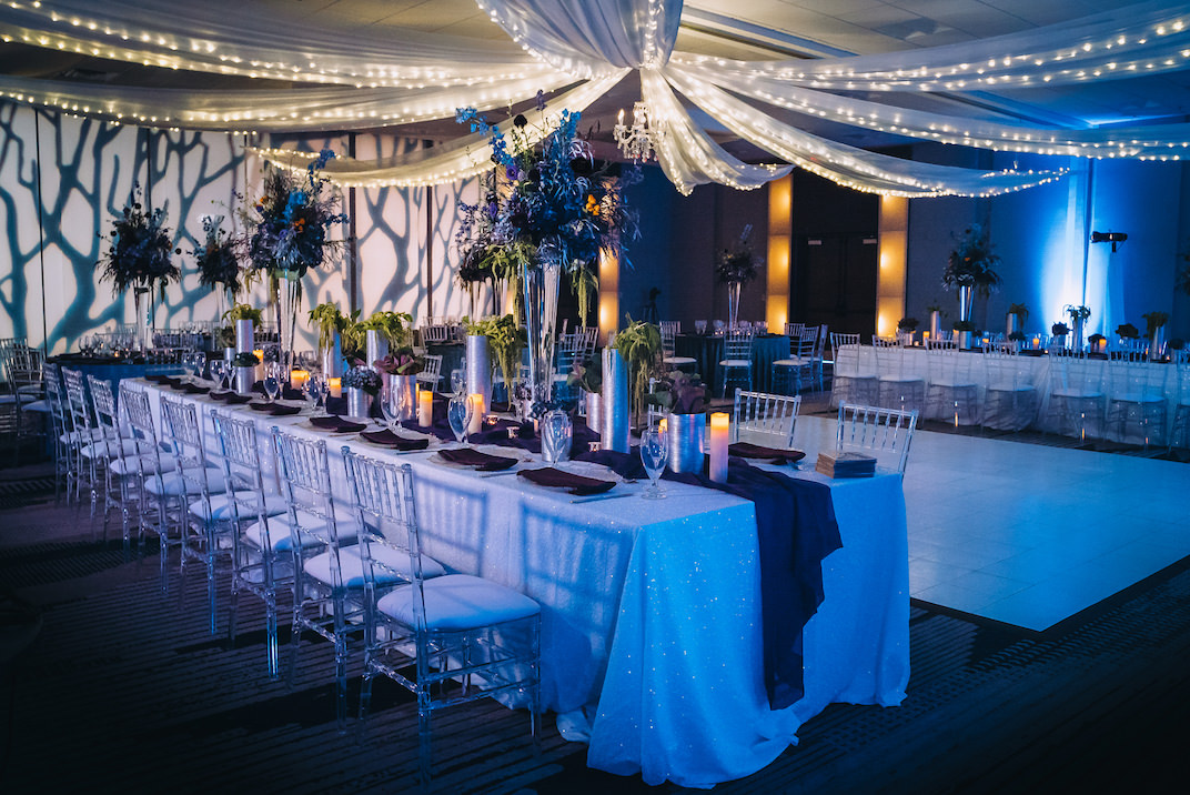 Dark Unique Modern Contemporary Dramatic Wedding Reception Decor, Long Feasting Tables with White Linens, String Lighting and White Linen Drapery, Tall Glass Vases with Unique Dark Blue, Purple Floral Centerpieces, Creative Artsy Wall Projection, Ghost Acrylic Clear Chiavari Chairs, Blue Table Runner | Tampa Bay Boutique Hotel Wedding Venue Hotel Alba | Wedding Planner Special Moments Event Planning | Wedding Rentals and Chair Decor Gabro Event Services | Styled Shoot