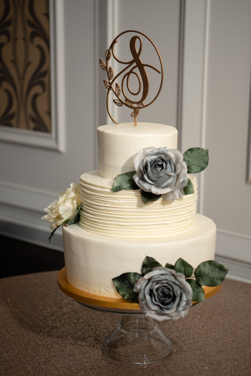 Classic, Elegant Three Tier Ivory Buttercream Wedding Cake with Textured Frosting, Dusty Blue Decorative Florals, Gold Custom Monogram Cake Topper