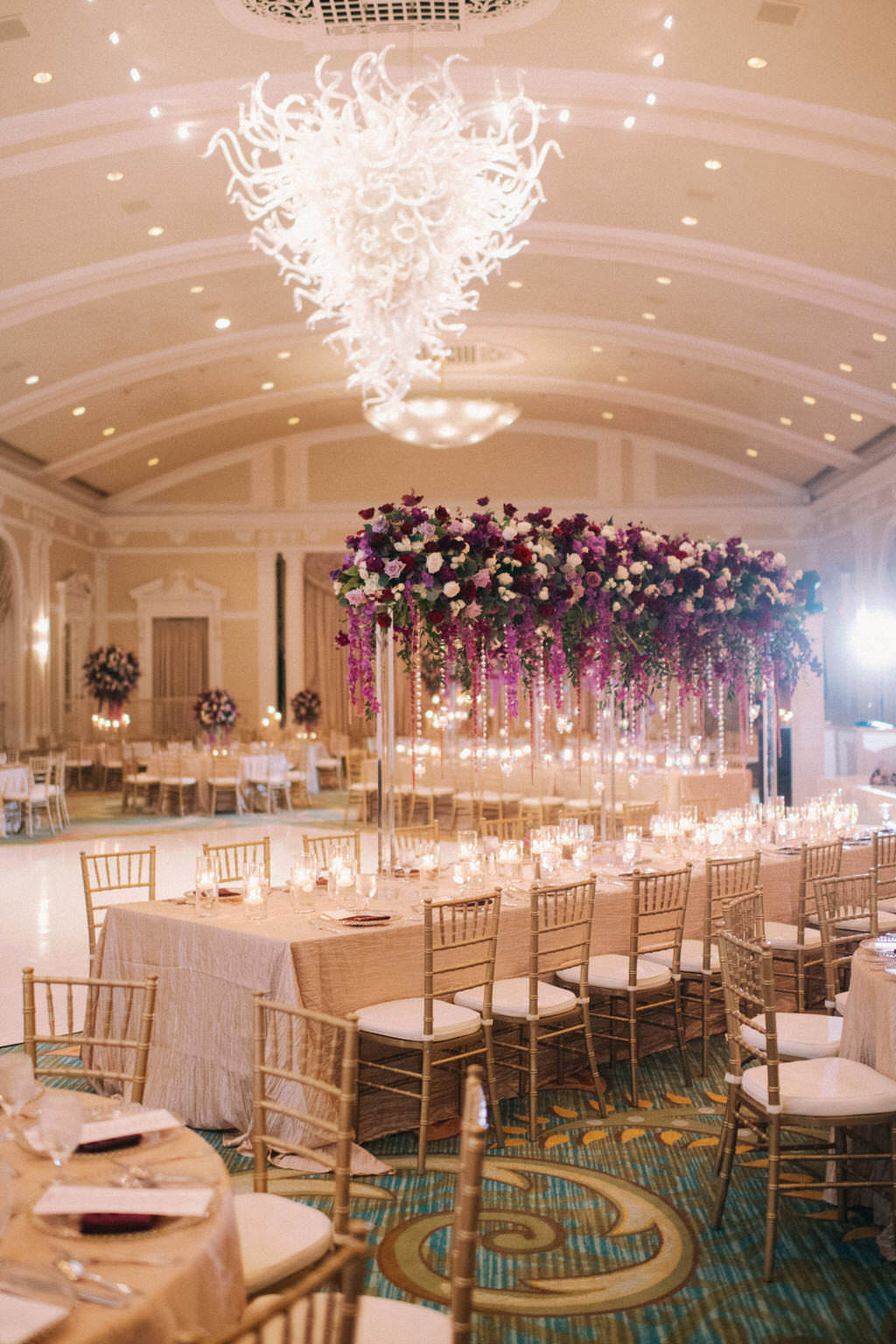 Elegant, Extravagant Wedding Reception Decor Portrait, Long Table with Gold Linen, Gold Chiavari Chairs, Tall Purple, Red, Plum, Lilac, Greenery and Purple Hanging Amaranthus Floral Centerpiece, Artistic Glass Chandelier | Downtown St. Pete Hotel Ballroom Wedding Venue The Vinoy Renaissance