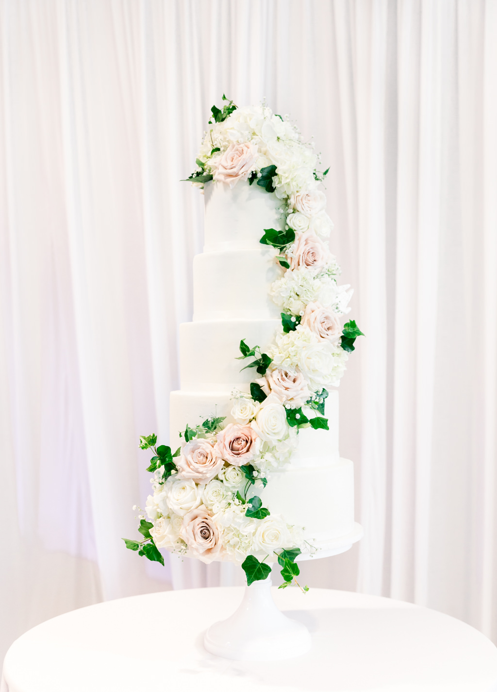Elegant Classic Six Tier Round White Wedding Cake with Cascading White Hydrangeas, Blush Pink Roses and Greenery Leaves   Tampa Wedding Baker The Artistic Whisk